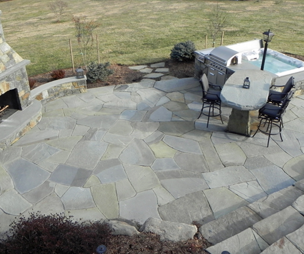 Stone deck with table, grill, and hot tub