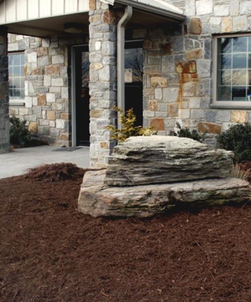 A boulder next to a stone building