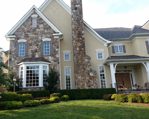 Large beige home with colored stone
