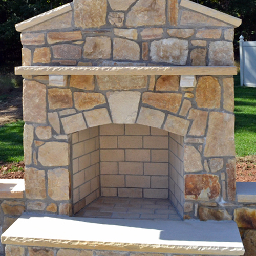 Reddish brown stone outdoor fireplace